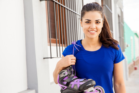 inline skater: Attractive young Hispanic skater carrying her inline skates on her shoulder and smiling