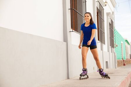 inline skater: Portrait of a happy young Hispanic woman working out and skating in the city