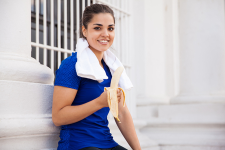 girl with towel: Beautiful Hispanic female athlete taking a break from running and eating a banana Stock Photo