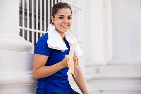 toallas: Hermosa mujer hispana atleta toma un descanso de correr y comer un plátano