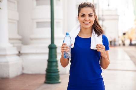 standing water: Portrait of a beautiful Latin woman relaxing and drinking water after jogging in the city