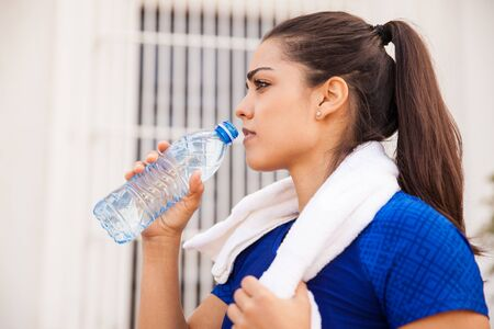 running water: Profile view of a gorgeous young Hispanic brunette drinking water from a bottle after running in the city