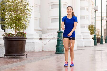 saltar la cuerda: Mujer latina linda que trabaja en la ciudad y que se divierte con una cuerda de saltar