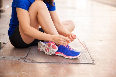 20s  closeup: Closeup of a young woman in sporty outfit tying her shoes before running outdoors Stock Photo