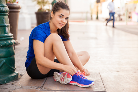lace up: Cute young Latin athlete tying her shoes and getting ready for a run in the city