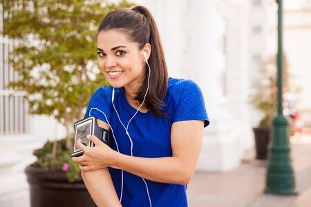 armband: Ritratto di una bella mora latina indossa il suo telefono cellulare in un bracciale e pronto per l'allenamento con un po 'di musica Archivio Fotografico
