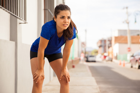 taking a break: Beautiful young brunette leaning on her knees and taking a break after a long run Stock Photo