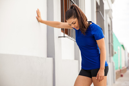 get a workout: Pretty brunette in sporty outfit taking a break and leaning against a wall to get some air after her workout Stock Photo