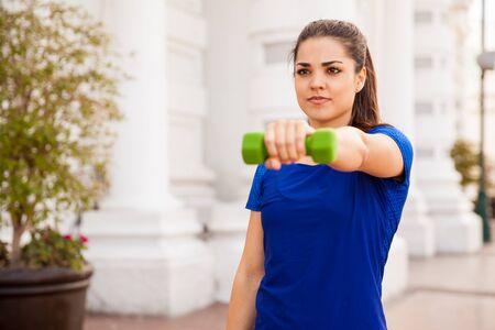 levantar pesas: Retrato de una hermosa joven de trabajo con pesas al aire libre Foto de archivo