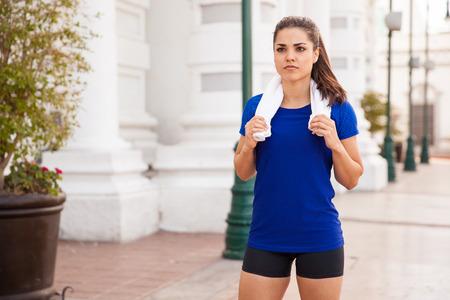 Beautiful female runner resting after her workout in the city holding a towel in her neck