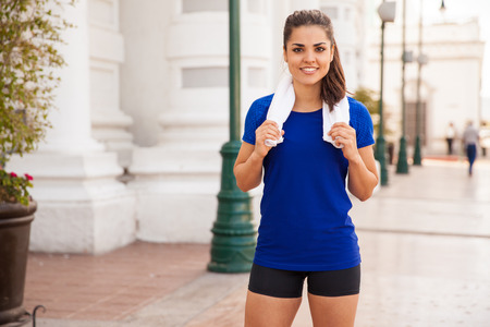 Cute young female runner with a towel around her neck resting after a long workout