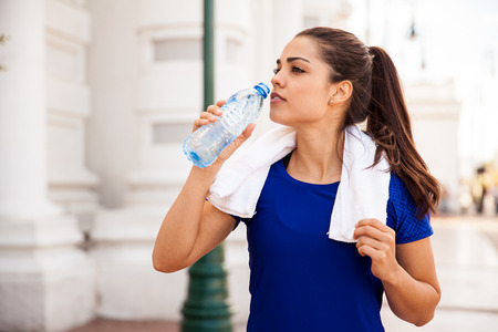 out of water: Pretty female runner resting and drinking water from a bottle after working out in the city