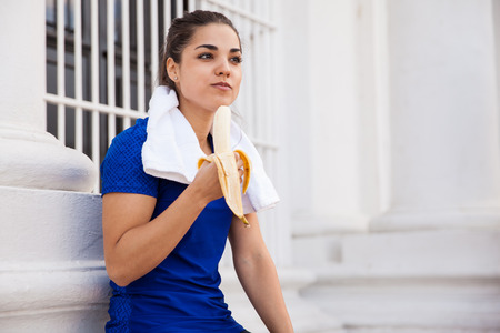 woman eating fruit: Cute active brunette relaxing after a long workout in the city and eating a banana Stock Photo