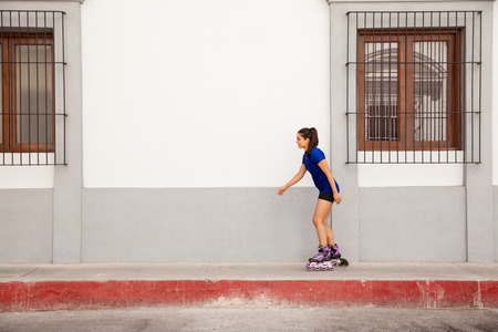 inline skater: Profile view of a cute young woman skating in the city