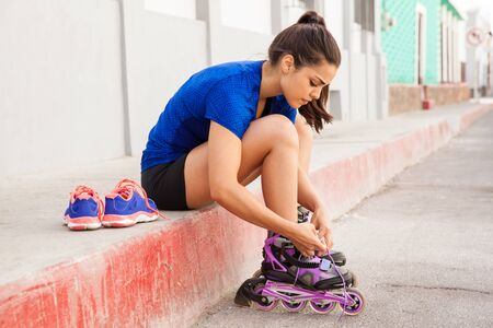 shoes off: Profile view of a woman sitting on the sidewalk and putting her inline skates on Stock Photo