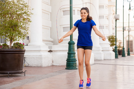 woman rope: Cute young woman jumping a rope as part of her workout in the city