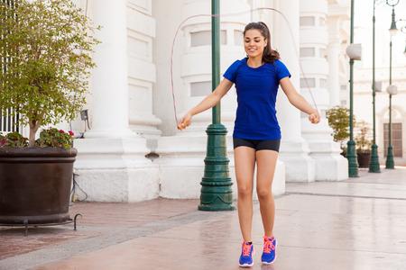saltar la cuerda: Mujer joven linda que salta una cuerda como parte de su entrenamiento en la ciudad