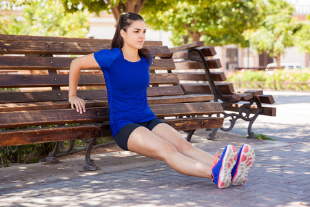 a workout: Pretty young woman concentrating on her workout leaning on a park bench Stock Photo