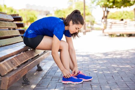 Profile view of a young woman tying her shoes in the park before going for a run
