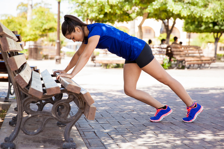 Pretty girl in sporty outfit doing some stretching exercises on a park bench Imagens