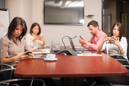 distracted: Group of people sitting in a meeting room and being distracted by their smartphones Stock Photo