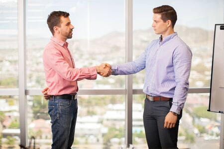 intimidating: Nervous young man giving a handshake to his confident and intimidating boss in his office Stock Photo