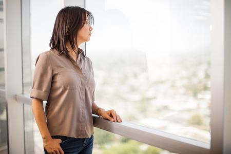 taking a break: Pretty young Latin woman taking a break from work and enjoying the office view Stock Photo