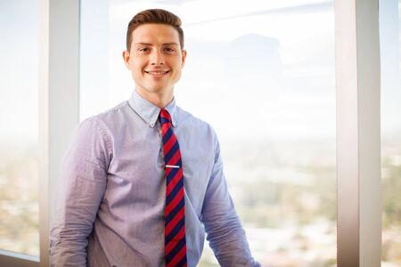 smiling businessman: Handsome young businessman standing in front of a window in a meeting room and smiling