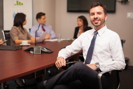 ley: Abogado joven hermoso con una corbata sentado con algunos de sus compañeros de trabajo en una sala de reuniones y una sonrisa