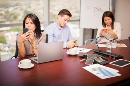 personas trabajando en oficina: Grupo de personas en una sala de reuniones que utilizan sus teléfonos inteligentes y haciendo caso omiso de trabajo por un tiempo Foto de archivo