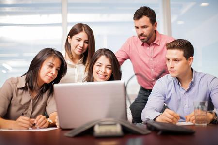 personas mirando: Retrato de un grupo de personas que buscan en un ordenador port�til y haciendo un trabajo en una oficina Foto de archivo