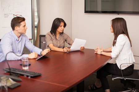 Cute Hispanic woman sitting in front of a couple of people during a job interview Banco de Imagens