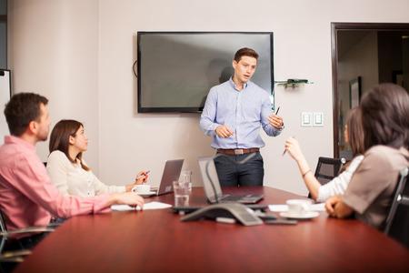 sala de reuniones: Hombre joven atractivo que lleva una reunión con sus colegas en una sala de conferencias Foto de archivo