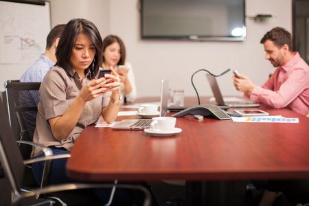 Grupo de personas en una sala de conferencias mensajes de texto y redes sociales en sus teléfonos celulares en lugar de trabajar Foto de archivo - 41597746