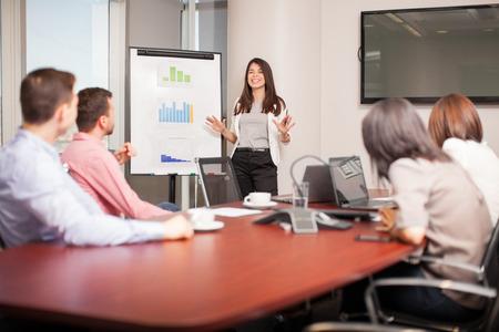 Mooie jonge Latijns-brunette geven van een zakelijke presentatie aan enkele van haar klanten in een vergaderruimte