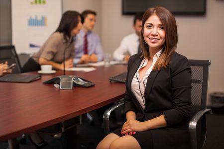 Porträt einer schönen Anwalt Frau in einem Konferenzraum sitzt mit einer Gruppe von Mitarbeitern
