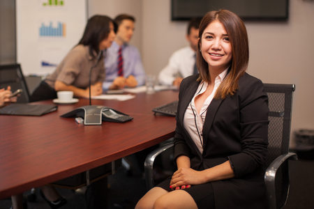 Portrait of a beautiful female lawyer sitting in a conference room with a group of coworkers Stock Photo