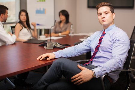 firm: Portrait of a confident and powerful lawyer sitting in a conference room with some of his colleagues Stock Photo