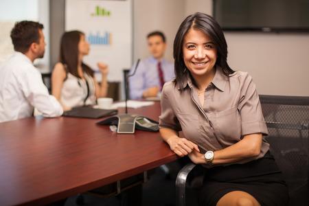 Hermosa joven abogado hispánica que se sienta en una sala de reuniones con algunos de sus colegas y sonriente