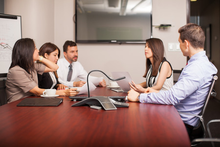 Group of five people in a meeting room in the middle of an important discussion