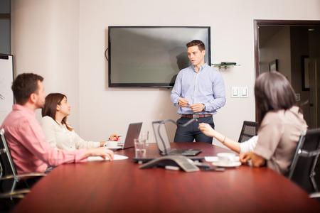 bel homme: Beau jeune homme habillé avec désinvolture et de donner un argument de vente dans une salle de réunion