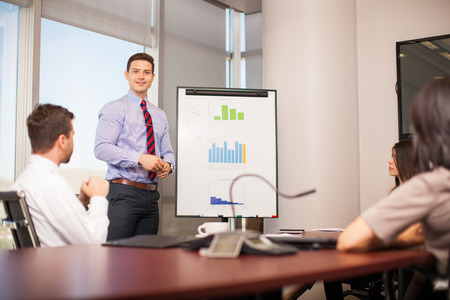 Portrait of an attractive young businessman giving a presentation to some of his clients in a meeting room