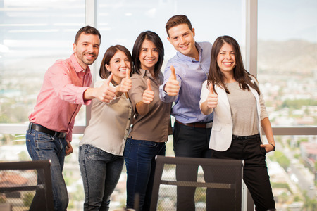 casual attire: Group of five Latin people in casual attire giving their thumbs up and smiling