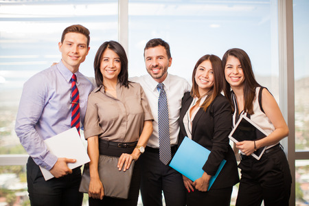 Group of young Hispanic business people in a meeting room taking a break from work and smiling
