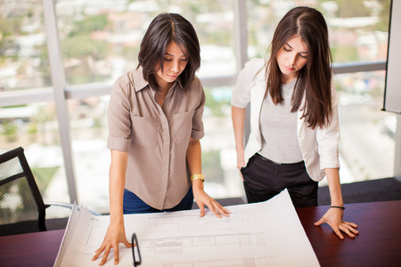 business project: Couple of female business partners analyzing a project together in a meeting room with a view