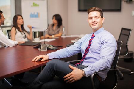 Atractiva joven abogado que se sienta en una sala de reuniones con algunos de sus compañeros de trabajo y sonriendo
