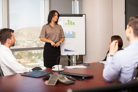 Pretty young woman giving a sales pitch to a group of business people in a meeting room