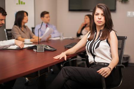 ley: Retrato de una abogada seguro y poderoso que se sienta en una sala de reuniones con algunos de sus clientes