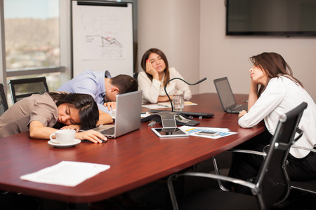 Group of people falling asleep in a meeting room after working too much