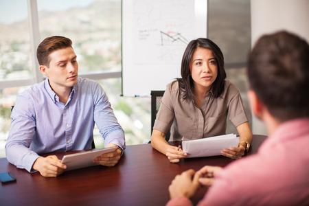 puesto de trabajo: Pares de los hombres latinos con el curriculum vitae en la mano de entrevistar a un candidato de trabajo en una sala de reuniones